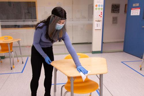 Alexander Academy staff sanitizing classroom