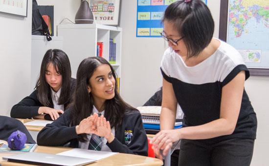 Alexander Academy students receiving help from teacher
